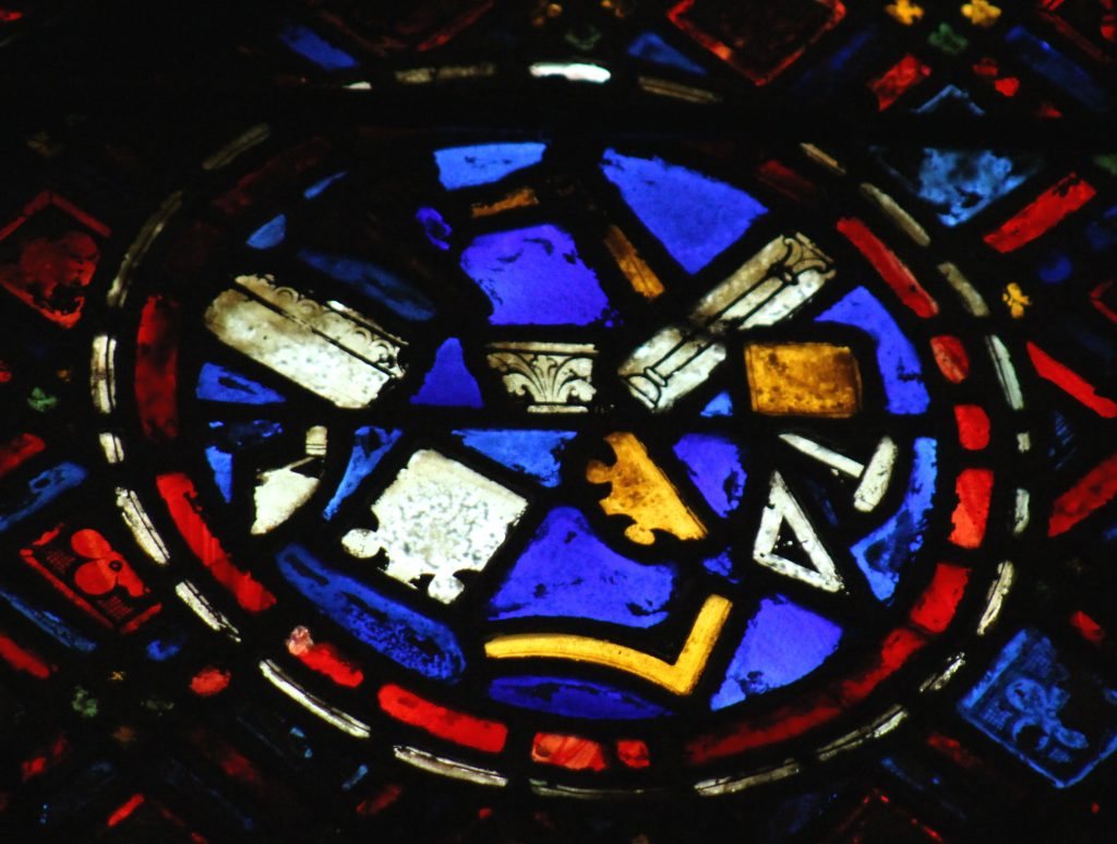 Image of glass panel depicting medieval masons' tools in the St Sylvester Window at Chartres Cathedral