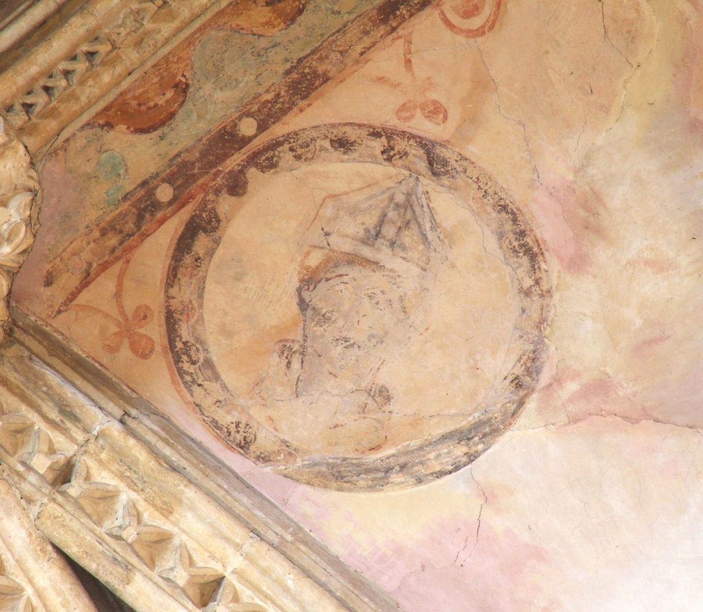 Image of painting of a bishop's head surrounded by a roundel in the south arm of the Great Transept at Lincoln Cathedral