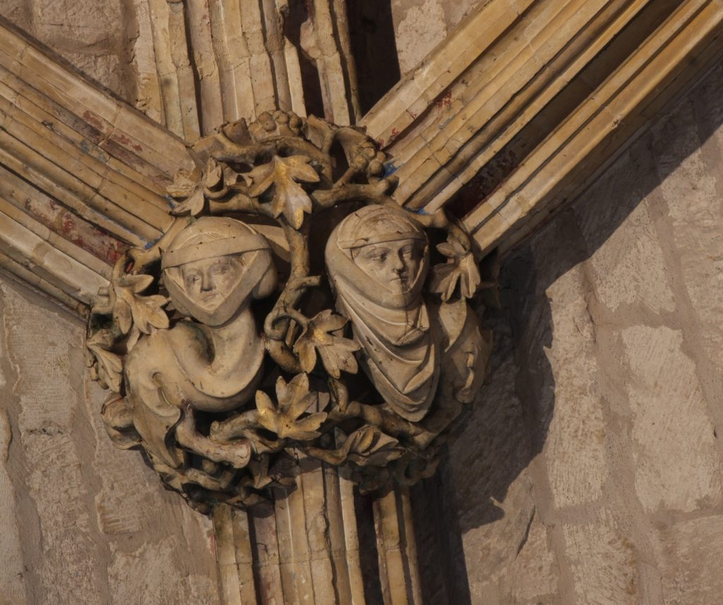 Image of boss in the Angel Choir aisle at Lincoln Cathedral, showing two serpentine creatures with long curving necks and the faces of women wearing wimples
