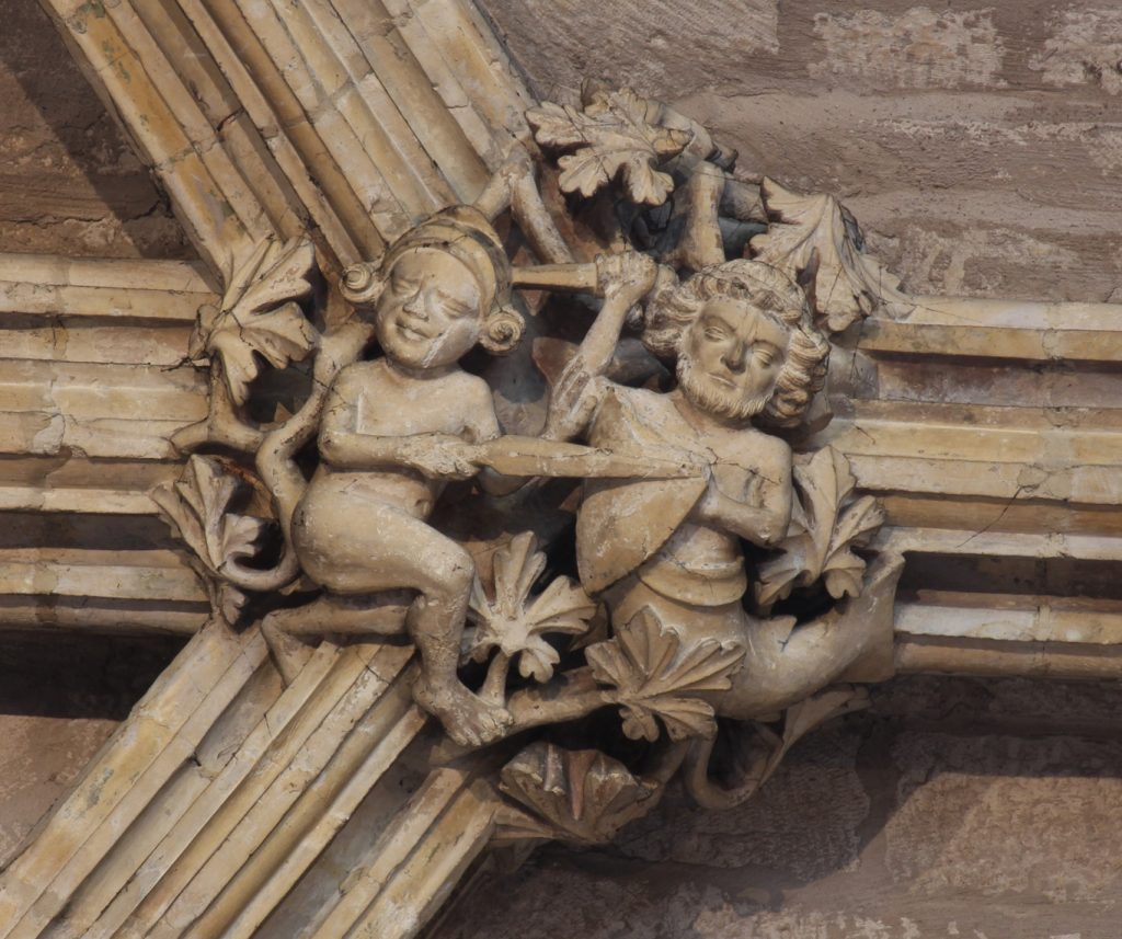 Image of boss in the Angel Choir aisle at Lincoln Cathedral, showing a fight between an armed naked man and a merman defending with sword and shield