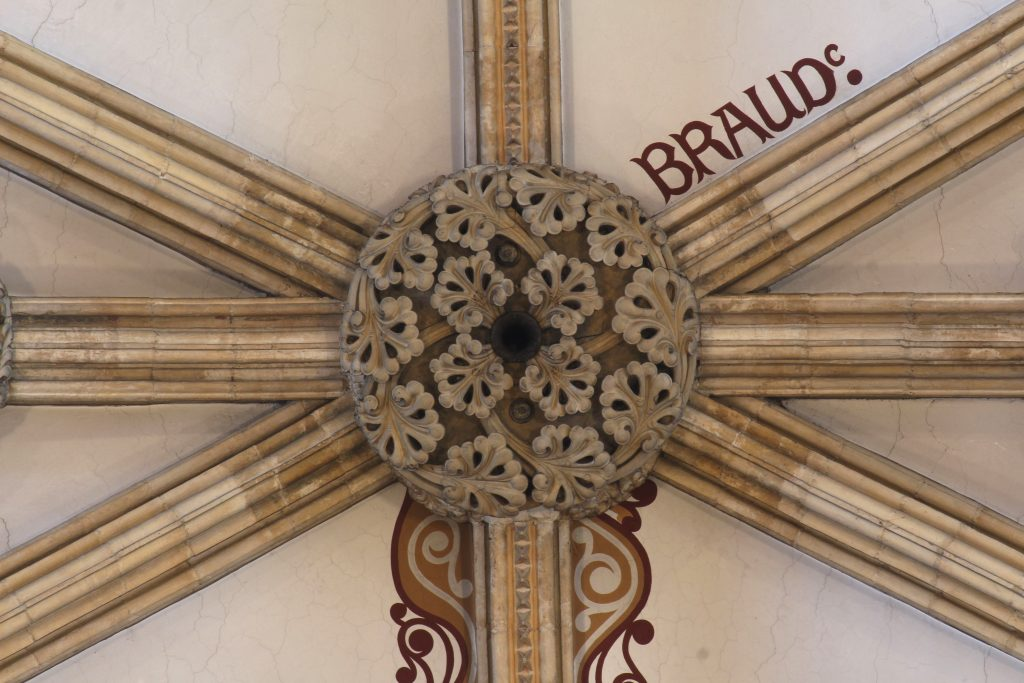 Image of central boss in the nave vault at Lincoln Cathedral, showing the name 'Braud'' painted on the adjacent webbing and painted scrollwork flanking the rib