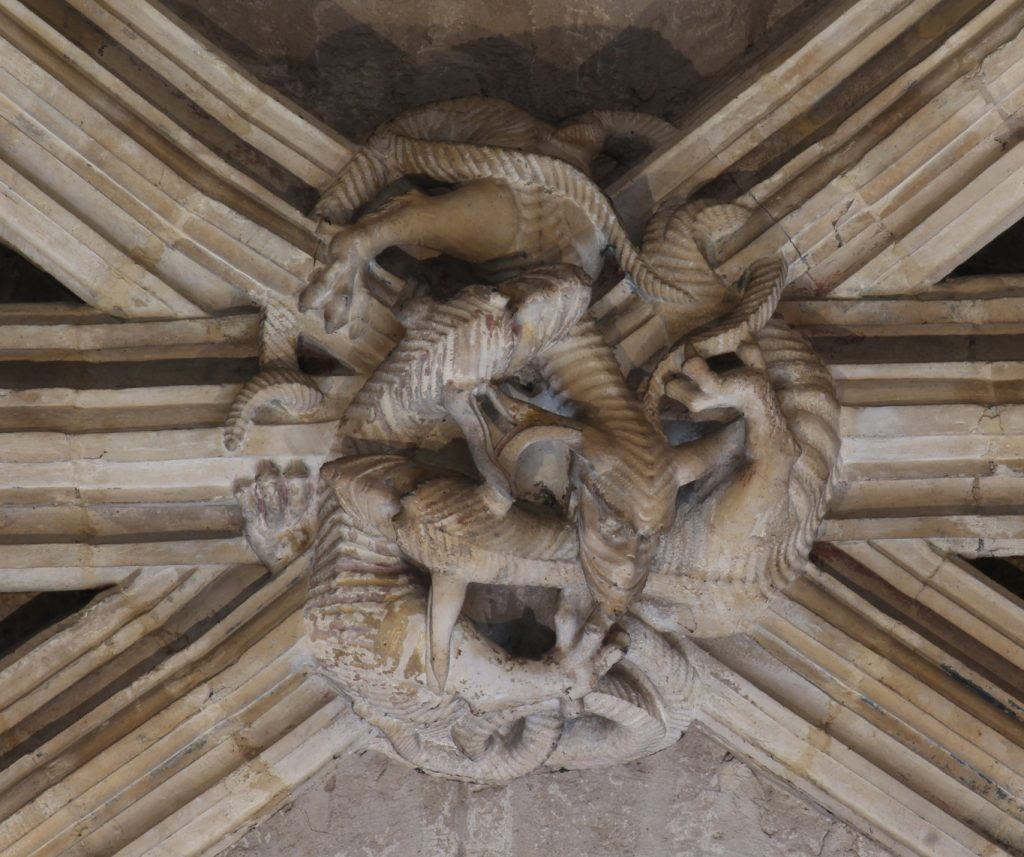Image of boss in the Angel Choir aisle at Lincoln Cathedral, showing a circular arrangement of three intertwining draconine creatures biting each other's necks and weacing their limbs and tails through the mouldings of the adjoining ribs